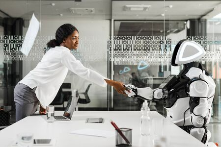 smiling african american businesswoman shaking hands with robot in office