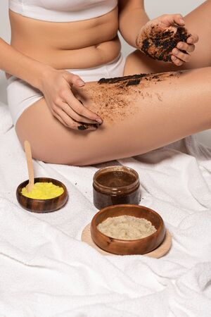 cropped view of girl with different scrubs applying coffee scrub on legs Foto de archivo