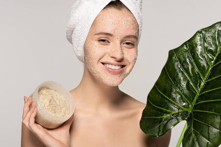 smiling girl with towel on head holding green leaf and plastic container with coconut scrub, isolated on grey Banque d'images