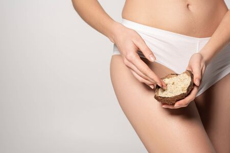 cropped view of young woman holding coconut scrub in coconut shell, isolated on grey