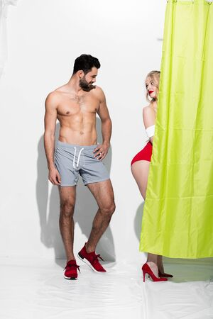 happy man looking at buttocks of seductive pin up girl standing near shower curtain on white Archivio Fotografico