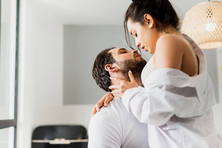 Side view of sensual woman in bra and shirt kissing handsome boyfriend in kitchen