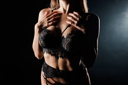 cropped view of seductive woman in lace underwear standing on black with smoke Imagens
