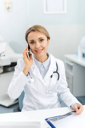 smiling doctor holding ultrasound scan and talking on smartphone in clinic