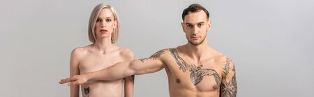 young naked tattooed couple isolated on grey, panoramic shot