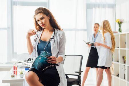 mise au point sélective d'une infirmière en blouse blanche tenant des lunettes et un magazine scientifique près des femmes en laboratoire