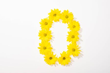 top view of yellow daisies arranged in letter O on white background