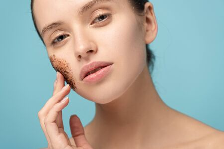 attractive woman applying coffee scrub on face, isolated on blue Banque d'images