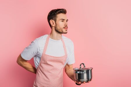 handsome young man in apron imitating waiter while holding saucepan on pink background