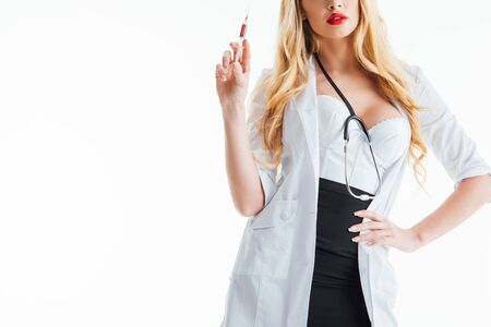 cropped view of blonde nurse holding syringe and standing with hand on hip on white