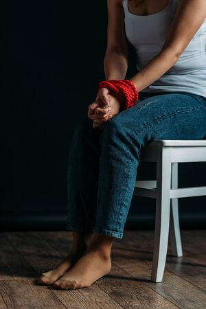 Cropped view of woman with tied hands sitting on chair on black background Banco de Imagens