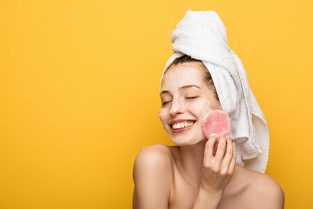 smiling girl with moisturizing facial mask holding cosmetic sponge isolated on yellow