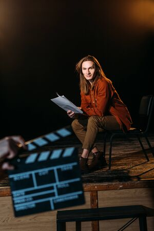 selective focus of young actor on stage with clapperboard in front Stockfoto