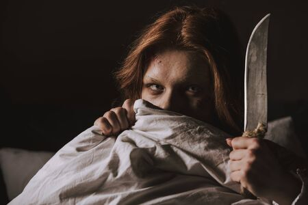 demonic obsessed evil girl holding knife in bed Stock Photo