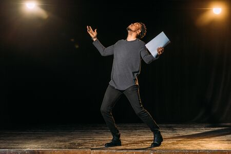 african american actor holding scenario and standing on stage during rehearse in theatre Imagens
