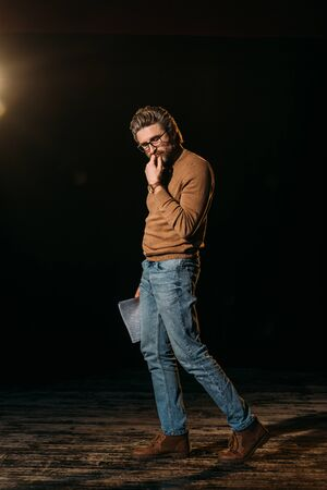 thoughtful mature actor holding scenario and standing on stage during rehearse Imagens