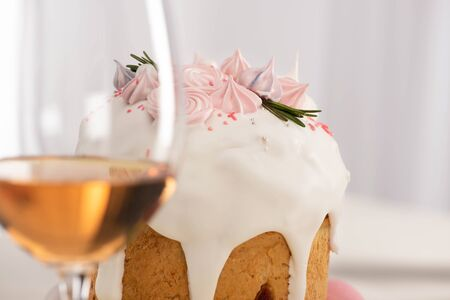 close up view of delicious Easter cake decorated with meringue near wine glass