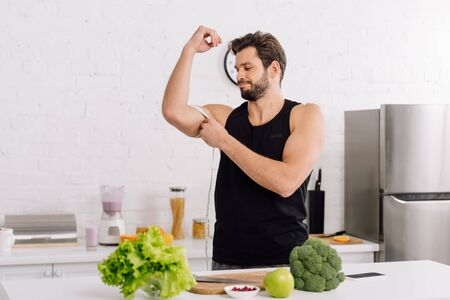 handsome and sportive man measuring muscle on hand near fresh food Stock Photo