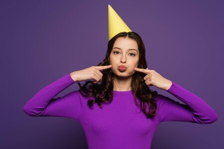 cheerful girl in party cap touching chicks with fingers on purple background
