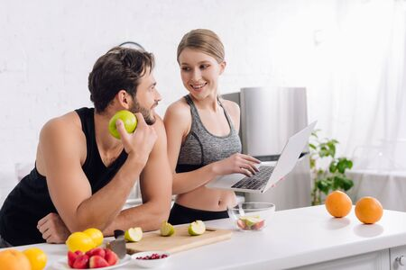 happy man with apple looking at woman with laptop near fruits Stock Photo