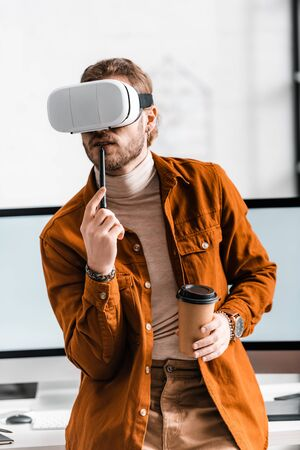 Digital designer in vr headset holding stylus of graphics tablet and coffee to go near computer monitors in office