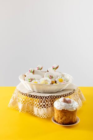 Delicious cookies in wicker basket on round board near easter cake isolated on grey