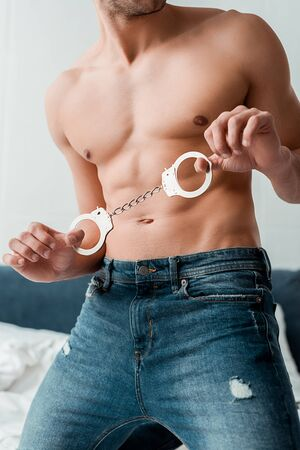 cropped view of submissive man in jeans holding handcuffs Stok Fotoğraf