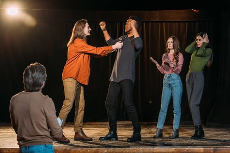 multiethnic actors rehearsing fight on stage in theatre