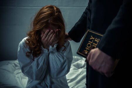 exorcist holding bible and hugging crying girl in bedroom