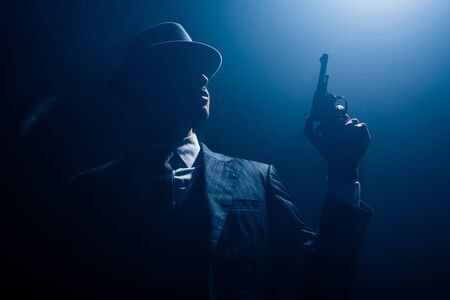 Low angle view of gangster silhouette holding gun and smoking on dark background