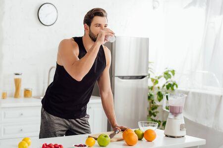bearded man drinking fresh smoothie near blender and fruits Stock Photo
