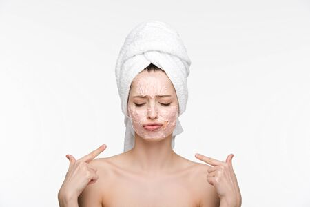 displeased pointing with fingers at peeling mask on face while standing with closed eyes isolated on white