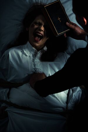 exorcist with bible and obsessed yelling girl in bedroom