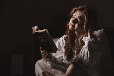creepy demoniacal crying woman reading holy bible on bed Archivio Fotografico