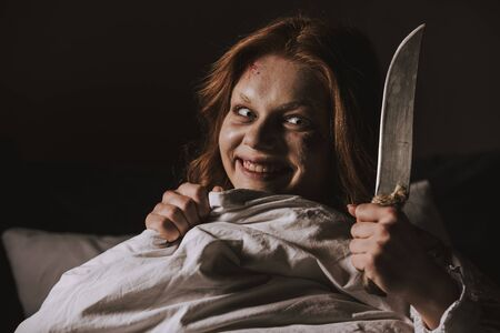 demoniacal smiling girl holding knife in bed Stock Photo