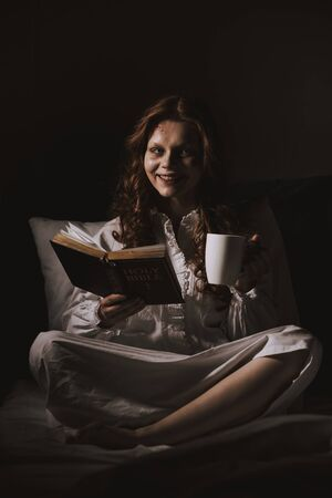demonic smiling woman in nightgown holding bible and cup on bed