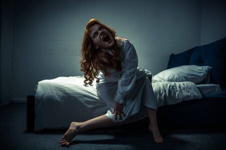 demonic creepy girl in nightgown shouting in bedroom Stock Photo