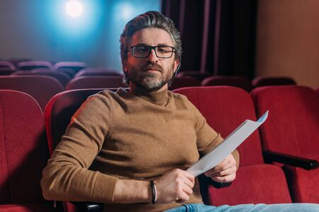 bearded stage director with scenario on seats in theater