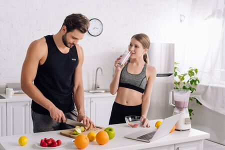 sportive girl drinking smoothie near man cooking in kitchen
