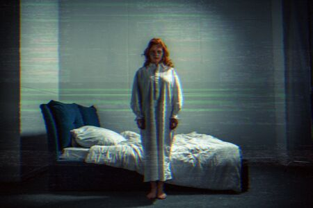 creepy demoniacal girl in nightgown standing in bedroom with tv noise