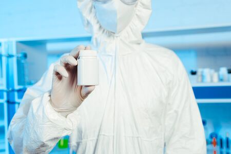 cropped view of scientist in hazmat suit holding bottle in laboratory