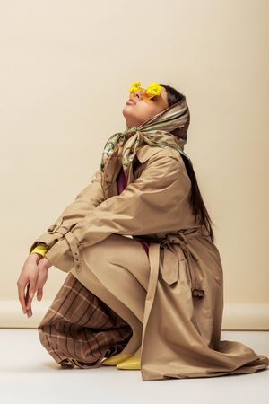 stylish african american girl in sunglasses with flowers, head scarf and trench coat sitting on beige