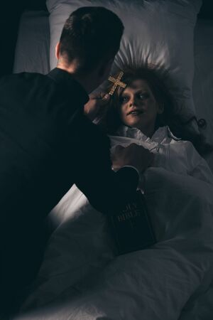 exorcist with bible and cross standing over obsessed girl in bed Stock Photo