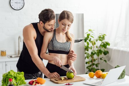 attractive girl cutting apple near sportive man, laptop and fruits in kitchen
