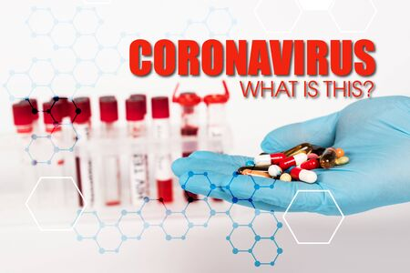 cropped view of scientist in latex glove holding pills near test tubes and coronavirus what is this lettering on white
