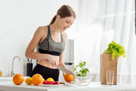 beautiful and sportive girl cutting orange near fruits and paper bag