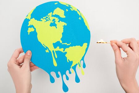 Cropped view of woman holding paper globe and match with fire on white, global warming concept