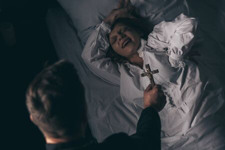 exorcist holding cross over demonic screaming girl in bed Stock Photo