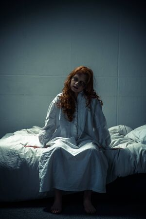 creepy demoniacal woman in nightgown sitting on bed Stock Photo