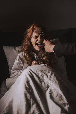 exorcist holding cross in front of obsessed yelling girl in bed